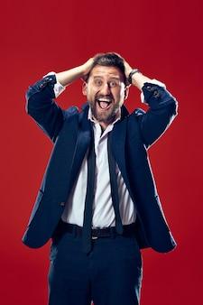 Ich habe gewonnen. erfolgreicher glücklicher mann, der feiert, ein gewinner zu sein. dynamisches bild des kaukasischen männlichen modells auf rotem studiohintergrund. sieg, freude konzept