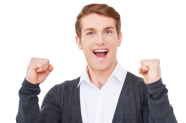 Ich habe gewonnen! glücklicher junger mann, der die arme erhoben hält und in die kamera schaut, während er isoliert auf weiß steht
