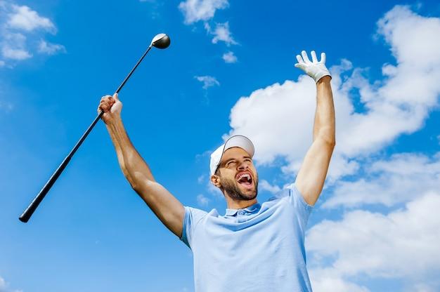 Ich habe gewonnen! niedrige winkelsicht des jungen glücklichen golfspielers, der fahrer hält und seine arme mit blauem himmel als hintergrund anhebt