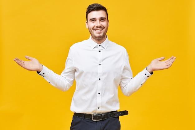 Ich habe keine ahnung. emotional attraktiver junger unrasierter mann, der glücklich lächelt, arme weit ausbreitet, begrüßungsgeste macht, präsentation zeigt, werbeprodukt an der kopyspace-wand
