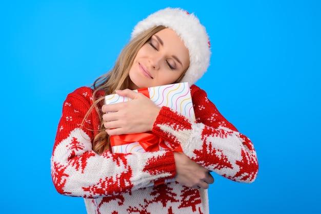 Ich habe so ein begehrtes geschenk vom weihnachtsmann bekommen! glückliche erstaunte niedliche schöne frau, die winterstrickpullover trägt, sie umarmt eine geschenkbox mit geschlossenen augen, lokalisiert auf hellblauem hintergrund