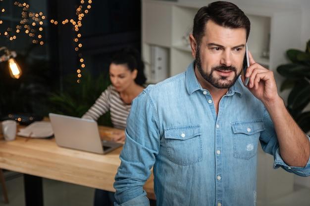 Ich höre zu. hübscher netter bärtiger mann, der den hörer abhebt und seinem gesprächspartner zuhört, während er im büro steht