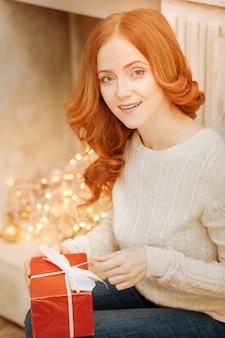 Ich kann es kaum erwarten, es zu öffnen. erstaunte reife rothaarige dame, die neben einem dekorativen kamin sitzt und ein schön verpacktes geschenk öffnet.