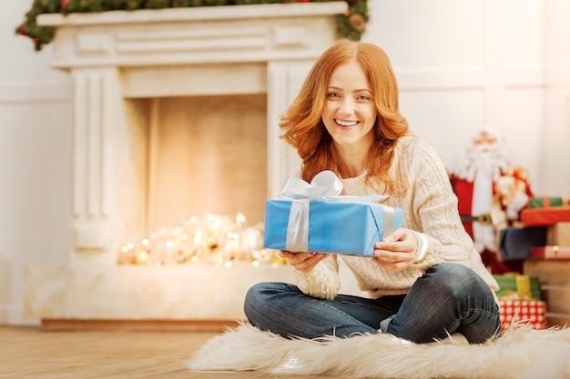 Ich kann es kaum erwarten, es zu öffnen. strahlende reife dame, die auf flauschigem teppich sitzt und breit grinst, während sie ein geschenk hält und weihnachtsmorgen zu hause genießt.