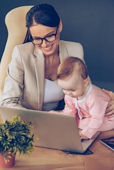 Ich kann ihnen helfen! draufsicht eines kleinen mädchens, das laptop benutzt, während es mit ihrer mutter im büro auf dem schreibtisch sitzt