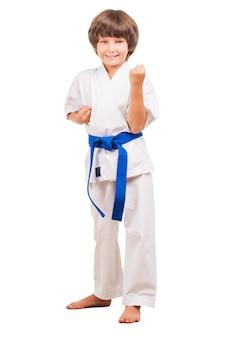 Ich kann mich verteidigen. volle länge des kleinen jungen in karate-uniform, der in karate-position steht, während er isoliert auf weiß steht