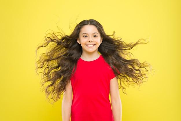 Ich lasse meine haare einfach los. glückliches kind mit fließendem haar auf gelbem hintergrund. kleines kind mit süßem lächeln und welligem, strukturiertem haar. entzückendes kleines mädchen, das mit dem langen brünetten haar lächelt.