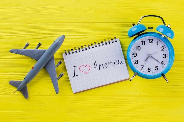 Ich liebe amerika, das auf notizblock geschrieben wird. flaches plastikflugzeug und wecker auf gelbem holztisch.