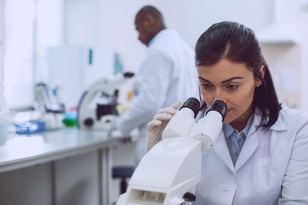 Ich liebe biologie. ernsthafter professioneller biologe, der eine uniform trägt und in das mikroskop schaut