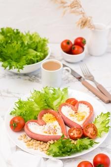 Ich liebe das frühstück. spiegeleier in herzförmigen würstchen, salat und kirschtomaten auf einem teller und einer tasse kaffee auf dem tisch. vertikale ansicht