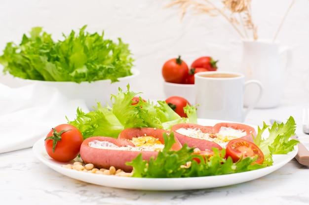 Ich liebe das frühstück. spiegeleier in herzförmigen würstchen, salat und kirschtomaten auf einem teller und einer tasse kaffee auf dem tisch
