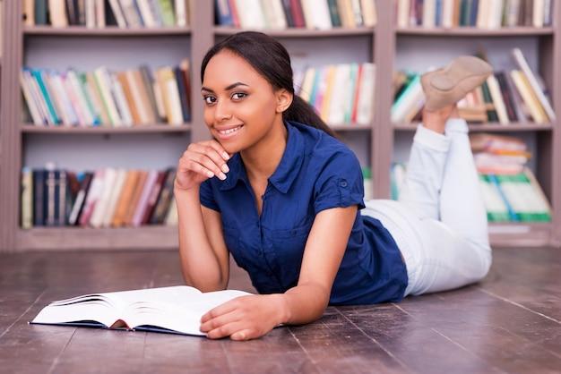 Ich liebe das lesen! fröhliche afrikanische studentin, die ein buch liest, während sie in der bibliothek auf dem boden liegt