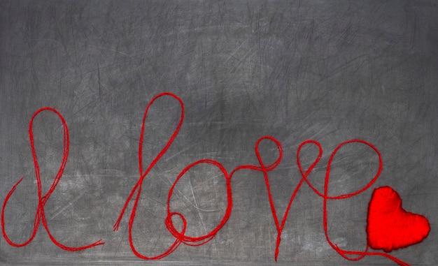 Ich liebe dich. die inschrift besteht aus rotem faden auf einer schwarzen tafel