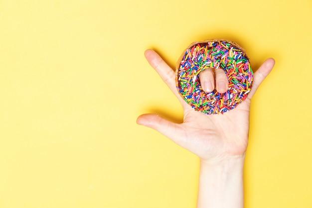 Ich liebe dich handzeichen mit schokoladengefrorenem donut mit streuseln, zuckerglasiert gefrostet auf gelbem hintergrund.