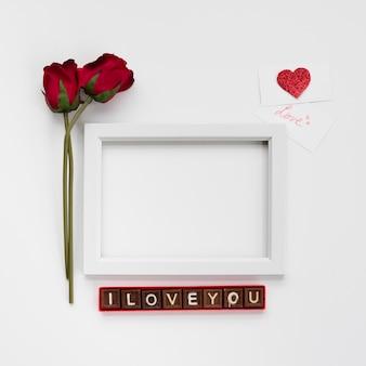 Ich liebe dich inschrift auf schokoladenstücken in der nähe von fotorahmen, blumen und karten