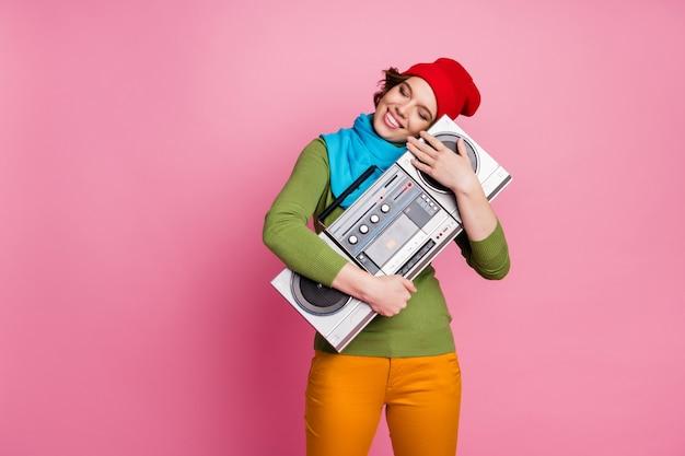 Ich liebe dich musik! friedliche fröhliche junge mädchen umarmung frühling boombox schließen augen traum rock party konzert tragen grün blau pullover gelbe hosen stil trendige hose isoliert rosa farbe wand