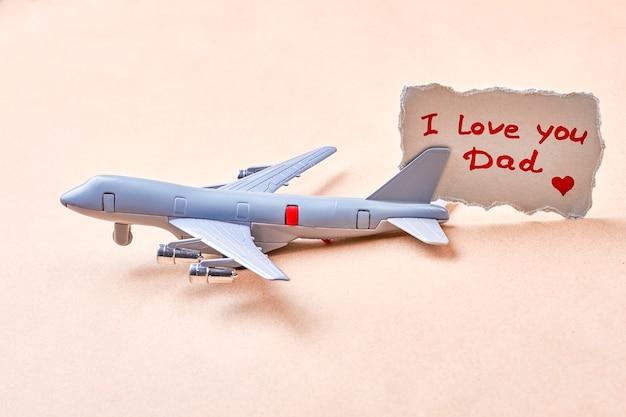 Ich liebe dich papa karte. spielzeugflugzeug in der nähe von grußpapier. kind in uns allen.