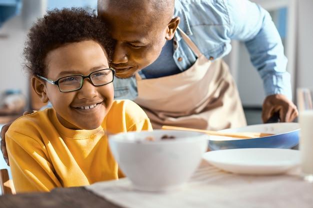 Ich liebe dich. sanfter junger vater, der liebevoll an das ohr seiner kleinen söhne flüstert, während der junge in der küche frühstückt