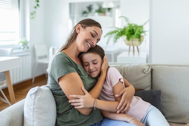 Ich liebe dich über alles. porträt einer glücklichen jungen mutter, die eine süße lächelnde kleine tochter im wohnzimmer huckepack trägt, ein liebevolles mädchen im schulalter, das geliebte tausendjährige weibliche kindermädchen oder pflegemutter umarmt