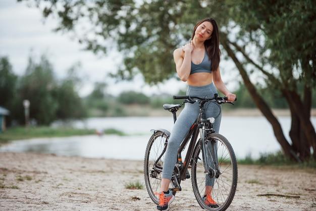 Ich liebe diesen ort. weibliche radfahrerin mit guter körperform, die mit ihrem fahrrad am strand am tag steht