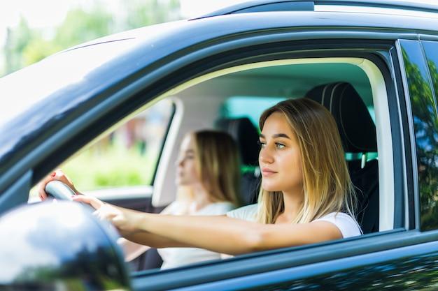 Ich liebe diesen roadtrip. zwei schöne junge fröhliche frauen mit lächeln beim sitzen im auto