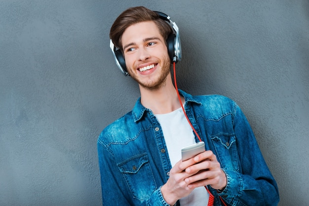 Ich liebe dieses lied. lächelnder junger mann mit kopfhörern mit handy