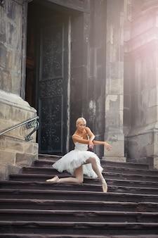 Ich liebe es, sie tanzen zu sehen. weichzeichneraufnahme einer ballerina, die auf ihrem knie posiert, die auf der treppe eines alten gebäudes steht