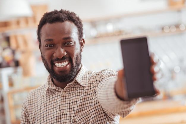 Ich liebe mein gerät. der fokus liegt auf einem angenehm fröhlichen mann, der im kaffeehaus steht und der kamera sein neues handy zeigt und sich über den kauf freut