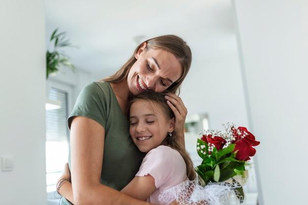 Ich liebe meine dich mama! attraktive junge frau mit kleinen süßen mädchen verbringen zeit zusammen zu hause und danken für handgemachte karte mit liebessymbol und blumen. glückliches familienkonzept. muttertag.