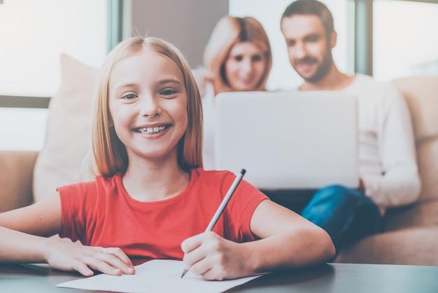 Ich liebe meine familie! glückliches kleines mädchen, das etwas auf papier zeichnet und lächelt, während ihre eltern mit laptop im hintergrund sitzen