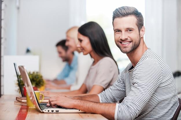 Ich liebe meinen job! gruppe fröhlicher geschäftsleute in intelligenter freizeitkleidung, die an ihren laptops arbeiten, während ein gutaussehender mann in die kamera schaut und lächelt