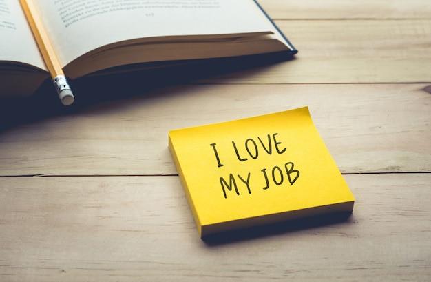 Ich liebe meinen jobtext mit briefpapier, notizblock und kaffeetasse auf dem schreibtisch am morgen