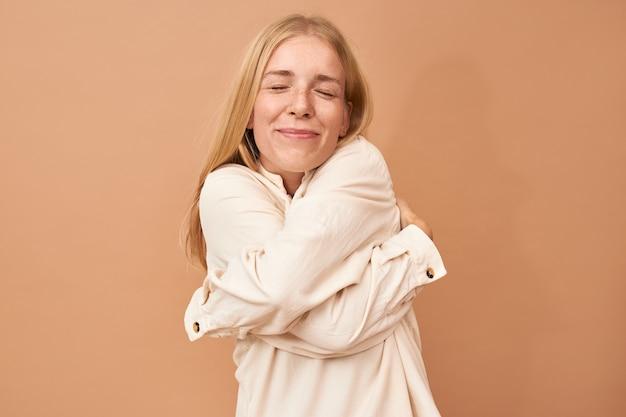 Ich liebe mich. schöne erfreute junge blonde frau mit hoher wertschätzung, die sich umarmt, arme um ihren körper hält und augen schließt
