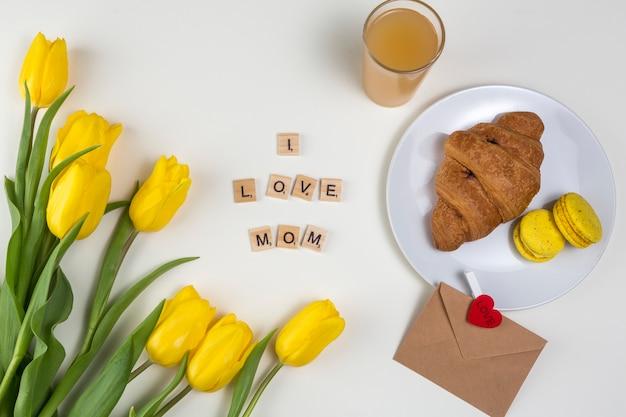 Ich liebe mom inschrift mit tulpen und croissant