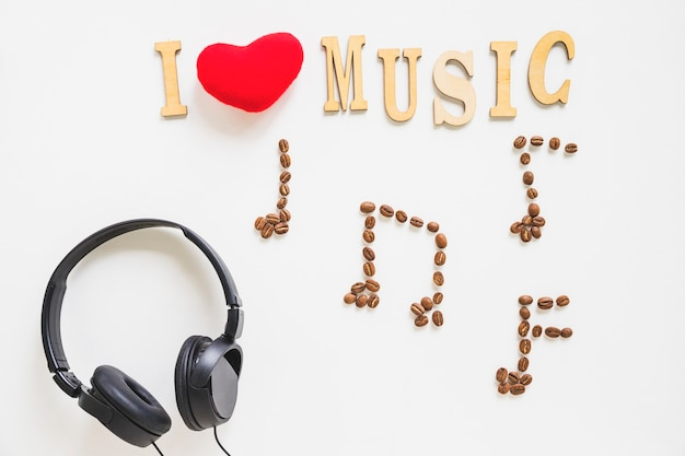 Ich liebe musiktext mit gebratenen musikalischen kaffeebohnen und kopfhörer auf weißem hintergrund