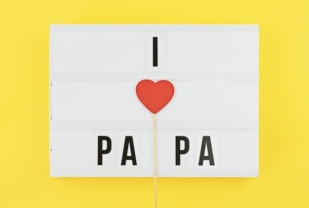 Ich liebe papatext auf weißem lightbox mit hölzernem herzen auf gelbem hintergrund