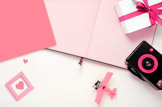 Ich liebe reisen. komposition mit fotoalbum, retro-hipster-kamera, rosa spielzeug und herz