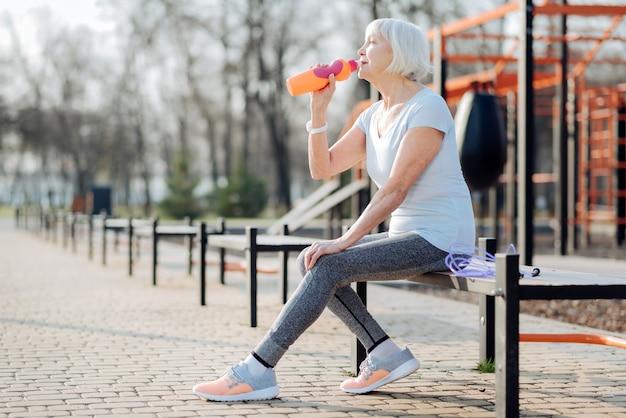 Ich liebe saft. zufriedene schlanke frau, die eine flasche saft hält und sich während des trainings entspannt