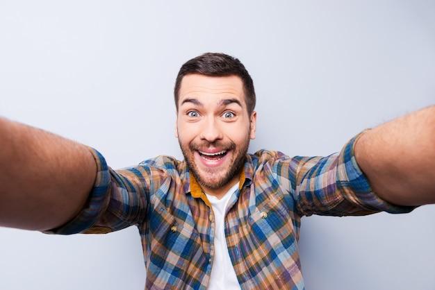 Ich liebe selfies! hübscher junger mann im hemd, der kamera hält und selfie macht und lächelt, während er vor grauem hintergrund steht