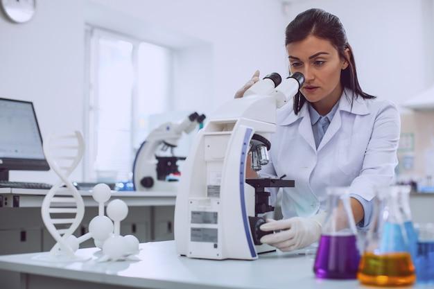 Ich liebe wissenschaft. konzentrierter professioneller biologe, der eine uniform trägt und in das mikroskop schaut