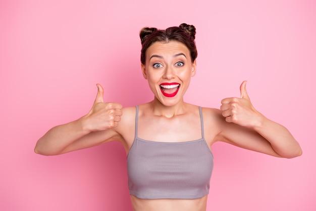 Ich mag das! foto der lustigen brötchen des erstaunlichen jungen mädchens, die daumenfinger anheben, die volle übereinstimmung ausdrücken tragen lässige graue kurze spitze isolierte rosa farbe