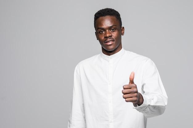 Ich mag das. junger attraktiver männlicher universitätsstudent mit afro-frisur im lässigen weißen t-shirt lächelnd, zeigt daumen oben in der kamera mit glücklichem und aufgeregtem ausdruck