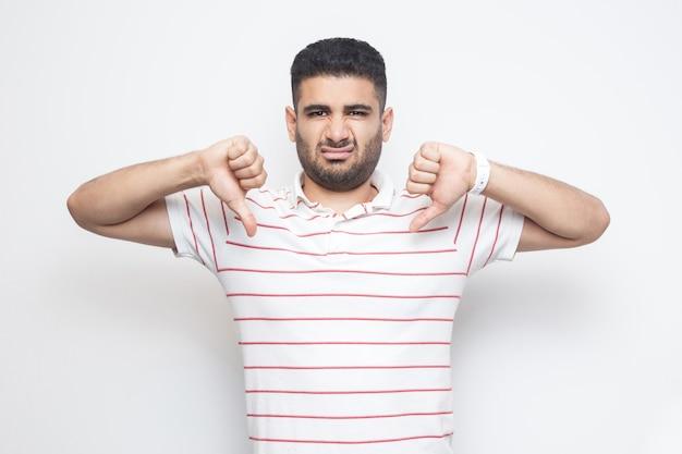 Ich mag das nicht. porträt eines unzufriedenen bärtigen jungen mannes in gestreiftem t-shirt, der mit daumen nach unten steht und keine zeichengeste mag und in die kamera schaut. indoor-studioaufnahme, isoliert auf weißem hintergrund.