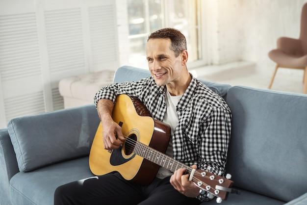 Ich mag musik. attraktiver freudiger gut gebauter mann, der lächelt und gitarre spielt, während er auf der couch sitzt