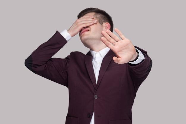 Ich möchte das nicht sehen. porträt eines verwirrten jungen mannes in violettem anzug und weißem hemd, stehend, schloss die augen mit den händen und zeigte stoppgeste. indoor-studioaufnahme, auf grauem hintergrund isoliert.