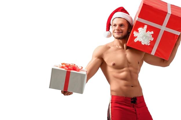 Ich möchte, dass du das nimmst. halblanges studioporträt eines wunderschönen sexy weihnachtsmannes, der eine geschenkbox hält und freudig lächelnd wegschaut