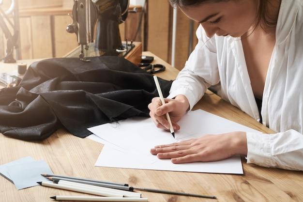 Ich muss es aufschreiben, bis es mir durch den kopf geht. konzentrierte kreative kleidungsdesignerin, die in der werkstatt sitzt und ein neues kleidungsprojekt zeichnet, das sie an der nähmaschine nähen wird. zuerst ist plan als nächstes - aktion