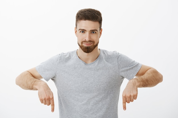 Ich muss es kaufen. selbstbewusster, enthusiastischer und kreativer charismatischer mann mit bart und braunem haarschnitt, der mit erhobenen armen nach unten zeigt und mit aufgeregtem entzücktem blick lächelt, der freund versichert, über graue wand zu versuchen