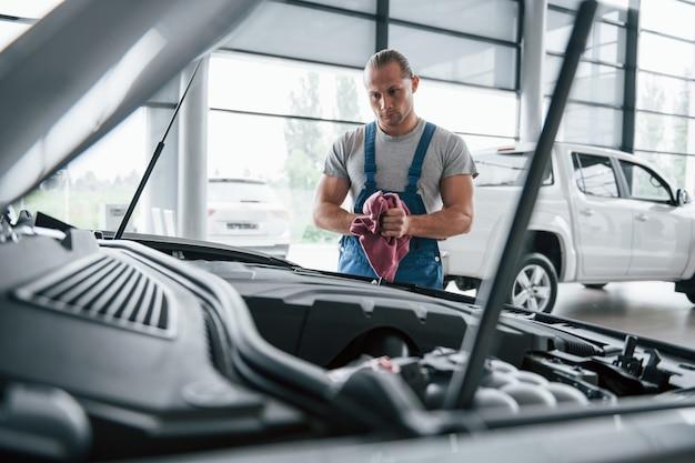 Ich muss genauer hinsehen. mann in blauer uniform arbeitet mit kaputtem auto. reparaturen durchführen