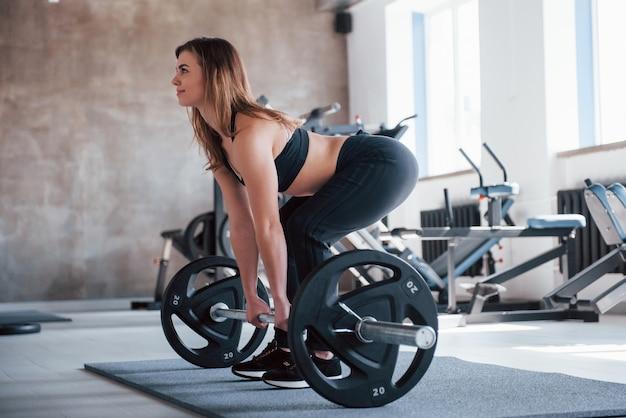 Ich muss mich konzentrieren. foto der herrlichen blonden frau im fitnessstudio zu ihrer wochenendzeit